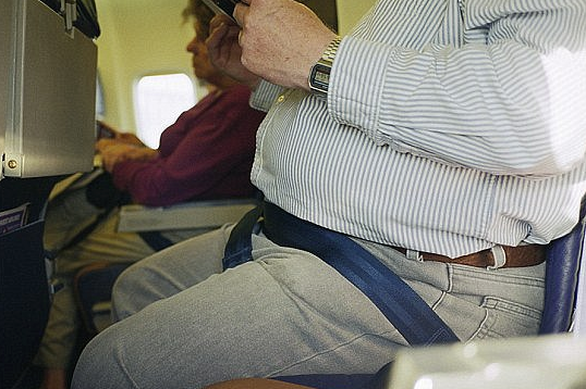 overweight traveler on airplane